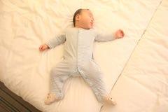 El pequeña caer asiática del bebé dormido en la cama imagen de archivo