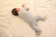 El pequeña caer asiática del bebé dormido en la cama imagen de archivo libre de regalías
