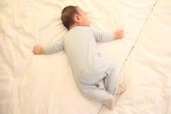 El pequeña caer asiática del bebé dormido en la cama fotos de archivo libres de regalías