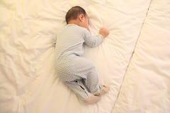 El pequeña caer asiática del bebé dormido en la cama fotografía de archivo libre de regalías