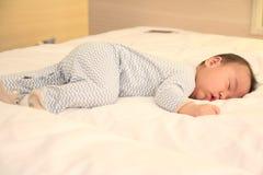 El pequeña caer asiática del bebé dormido en la cama imagenes de archivo
