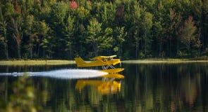El pequeño aeroplano amarillo en pontón saca de un lago Imagen de archivo libre de regalías