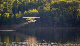 El pequeño aeroplano amarillo en pontón saca de un lago Foto de archivo