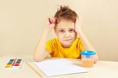 El pequeño artista preocupado en camisa amarilla está pensando qué dibujar Foto de archivo libre de regalías