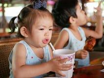 El pequeño ` asiático s del bebé da la elevación encima de una taza llenada de agua que aprende beber el agua de una taza con la  fotografía de archivo libre de regalías