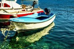 El pequeño barco de pesca reflejó en el agua clara del mar Mediterráneo Fotografía de archivo libre de regalías