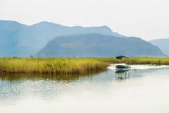 El pequeño barco fisging va en la costa costa por mañana tranquila Foto de archivo