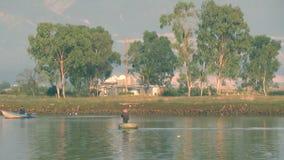 El pequeño barco redondo vietnamita de la cesta flota en el río Dos barcos Cigüeña blanca almacen de metraje de vídeo