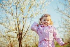 El pequeño bebé 3 años, esos corre entre el outd de los árboles florecientes Fotografía de archivo libre de regalías
