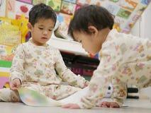 El pequeño bebé asiático dejó la apertura de un libro para sí misma y su hermana del bebé imagenes de archivo