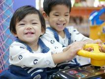 El pequeño bebé asiático dejado goza el jugar del juego de arcada con su más vieja hermana imagen de archivo libre de regalías