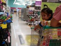 El pequeño bebé asiático en un carro de la compra, consigue excitado para ver muchas bicis en diversos colores en un supermercado foto de archivo libre de regalías