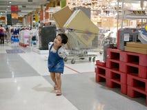 El pequeño bebé asiático está en un buen humor y goza el caminar en una alameda de compras fotos de archivo libres de regalías