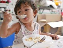 El pequeño bebé asiático goza el comer de la comida sola fotos de archivo libres de regalías