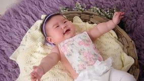 El pequeño bebé asiático miente en pesebre de la cesta en vestido y venda metrajes
