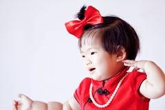 El pequeño bebé chino feliz en cheongsam rojo se divierte Imagen de archivo libre de regalías