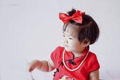 El pequeño bebé chino feliz en cheongsam rojo se divierte Foto de archivo