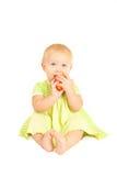 El pequeño bebé come el melocotón rojo Foto de archivo