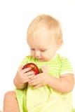 El pequeño bebé come la manzana roja Fotografía de archivo