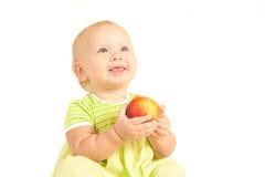 El pequeño bebé come la sonrisa roja del melocotón Imagen de archivo