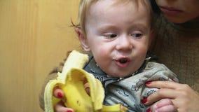 El pequeño bebé come el plátano con sus madres ayuda, sentándose en sus rodillas metrajes