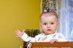 El pequeño bebé con el arco en su cabeza juega en el pesebre Fotos de archivo