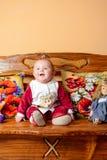 El pequeño bebé con una cola se sienta en un sofá con las almohadas y los juguetes bordados fotos de archivo libres de regalías