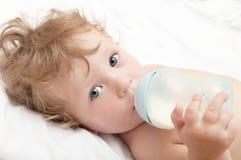 El pequeño bebé de pelo rizado chupa una botella de leche Imagenes de archivo