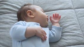 El pequeño bebé dulce está durmiendo con su finger en su boca metrajes
