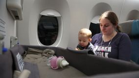 El pequeño bebé en el avión en las manos de la madre juega con el juguete Primera vez del niño infantil en vuelo y viaje almacen de metraje de vídeo