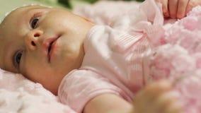 El pequeño bebé en un vestido rosado miente en una cama almacen de video