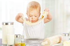 El pequeño bebé está cocinando, amasa la hornada de la pasta Imagen de archivo