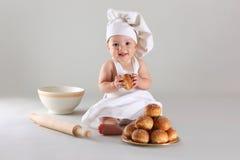El pequeño bebé feliz en un casquillo del cocinero ríe Foto de archivo