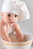 El pequeño bebé feliz en un casquillo del cocinero ríe Imagenes de archivo