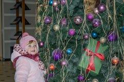 El pequeño bebé feliz es hermoso en un abrigo de pieles blanco, sombrero, bufanda cerca de un árbol de navidad adornado con los j Imágenes de archivo libres de regalías