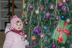 El pequeño bebé feliz es hermoso en un abrigo de pieles blanco, sombrero, bufanda cerca de un árbol de navidad adornado con los j Fotos de archivo libres de regalías