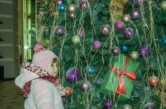 El pequeño bebé feliz es hermoso en un abrigo de pieles blanco, sombrero, bufanda cerca de un árbol de navidad adornado con los j Foto de archivo libre de regalías