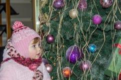 El pequeño bebé feliz es hermoso en un abrigo de pieles blanco, sombrero, bufanda cerca de un árbol de navidad adornado con los j Fotografía de archivo libre de regalías