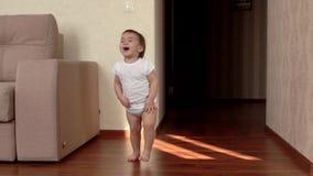 El pequeño bebé hace los primeros pasos en casa y las risas en la cámara lenta metrajes