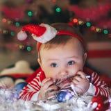 El pequeño bebé hermoso en el sombrero de Papá Noel celebra la Navidad y el juego con la guirnalda Días de fiesta del ` s del Año Foto de archivo libre de regalías