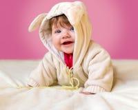 El pequeño bebé hermoso en un traje divertido con los oídos ríe, mintiendo en su estómago Imagen de archivo