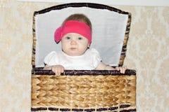 El pequeño bebé hermoso se sienta en cesta de mimbre grande Foto de archivo
