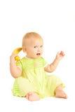 El pequeño bebé joven come el plátano amarillo    Imagen de archivo