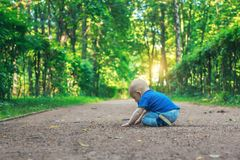 El pequeño bebé lindo con la entrerrosca se sienta en el sendero en el bosque dreamlike todo solamente Niño pequeño que se sienta imágenes de archivo libres de regalías