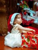 El pequeño bebé lindo en el sombrero de Stana abre su primera Navidad pre Fotografía de archivo libre de regalías