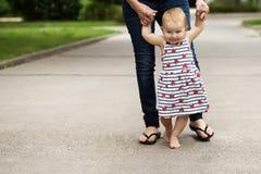 el pequeño bebé lindo, lleva sus primeras medidas, aferrándose su madre Foto de archivo