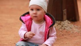 El pequeño bebé lindo se vistió en la ropa rosada que se sentaba en el patio en al aire libre almacen de metraje de vídeo