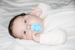El pequeño bebé miente en la hoja blanca en cama Fotos de archivo