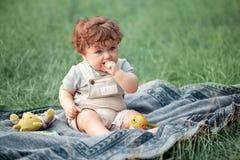 El pequeño bebé o el niño año en la hierba en día de verano soleado Imagen de archivo libre de regalías