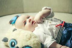 El pequeño bebé pensativo chupa un finger en una boca Fotos de archivo